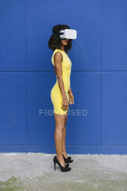 Woman in yellow dress wearing Virtual Reality Glasses against blue background — Stock Photo