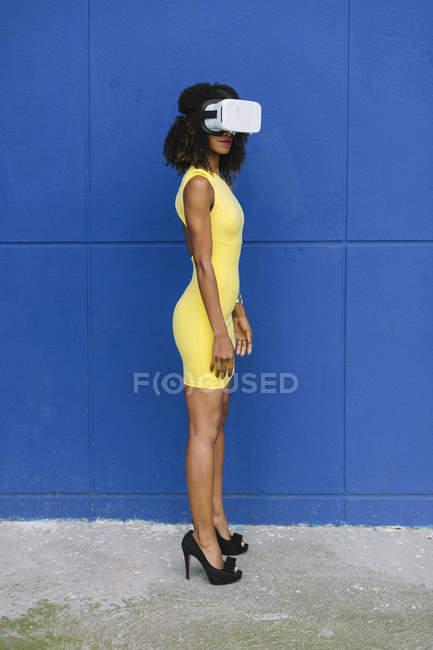 Donna in abito giallo con occhiali Virtual Reality sullo sfondo blu — Foto stock