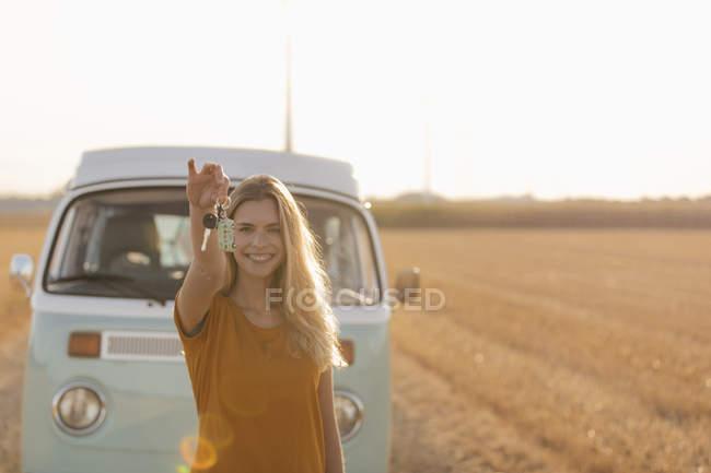 Happy young woman holding car key at camper van in rural landscape — стокове фото