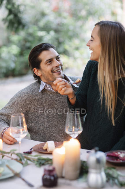 Happy couple having a romantic candlelight meal at garden table — Stock Photo