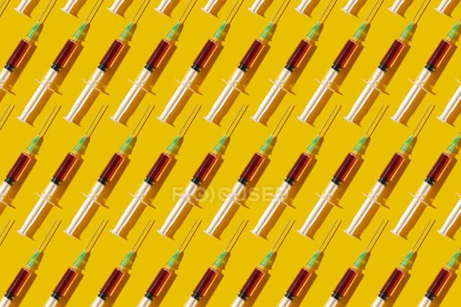 Múltiples jeringuillas organizadas en un patrón sobre fondo amarillo - foto de stock