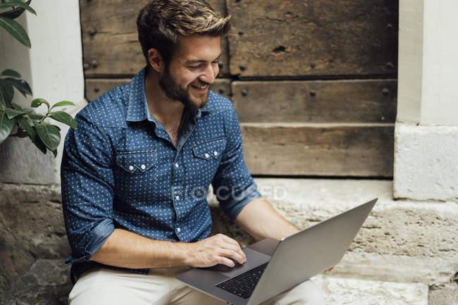 Empresário sorridente sentado em degraus em um pátio e usando laptop — Fotografia de Stock