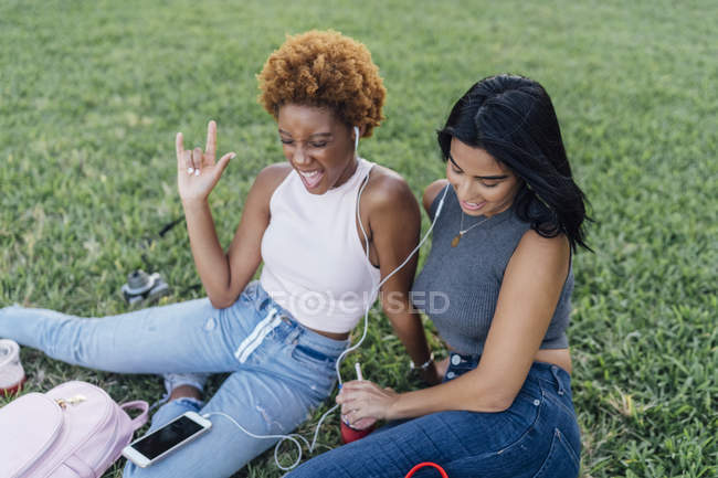 Dos amigas felices relajándose en un parque y escuchando música - foto de stock