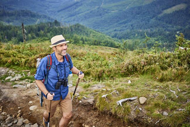 Lächelnder Mann beim Wandern in den Bergen — Stockfoto