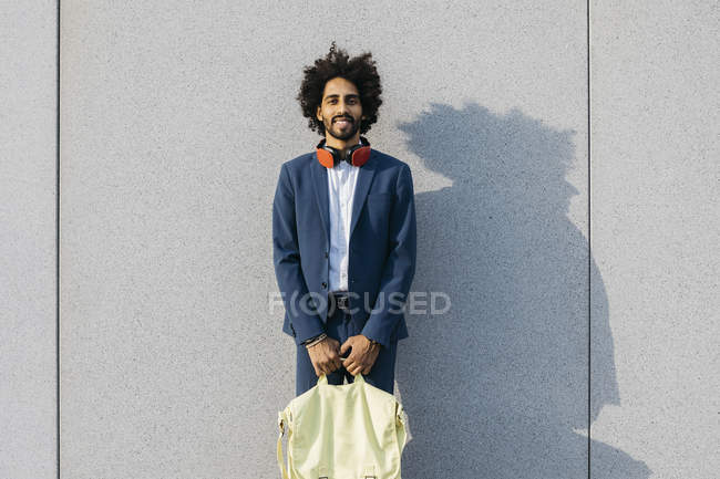 Portrait of smiling young businessman with bag and headphones at a wall — Stock Photo