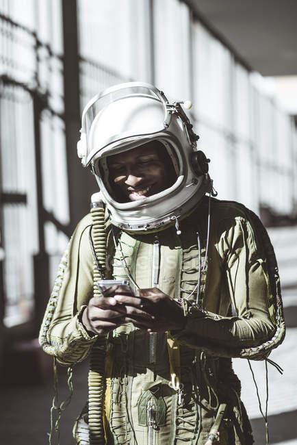 Smiling astronaut in spacesuit using smartphone — Stock Photo