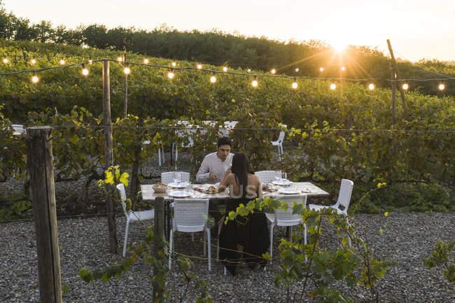 Italie, Toscane, Sienne, jeune couple dînant dans un vignoble — Photo de stock