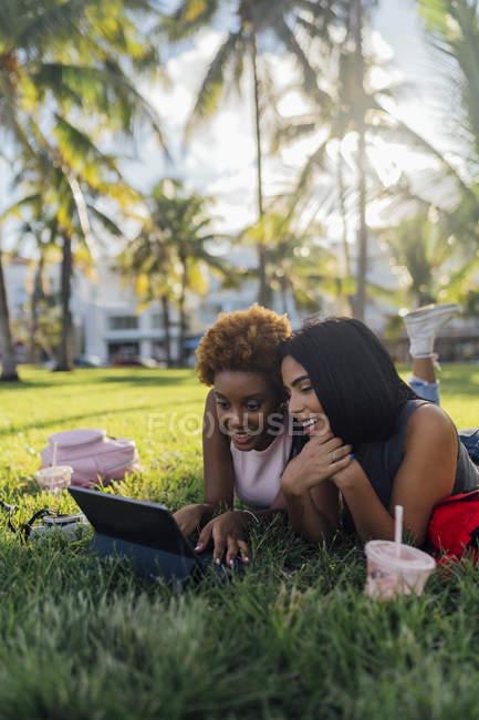 Duas amigas felizes relaxando em um parque e usando um tablet — Fotografia de Stock