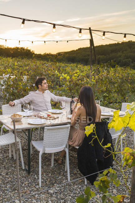 Italy, Tuscany, Siena, young couple having dinner in a vineyard — Stock Photo