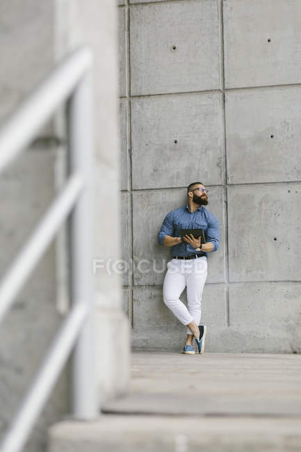 Bearded hipster businessman with digital tablet leaning against wall and looking at distance — стокове фото