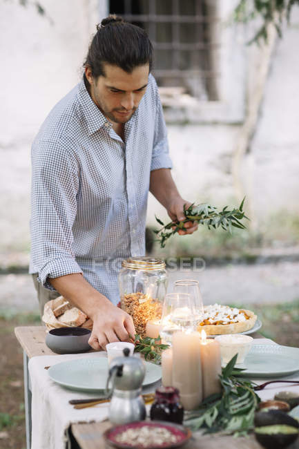 Man preparing a romantic candlelight meal outdoors — Stock Photo