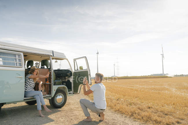 Happy young couple taking cell phone picture at camper van in rural landscape — Stock Photo