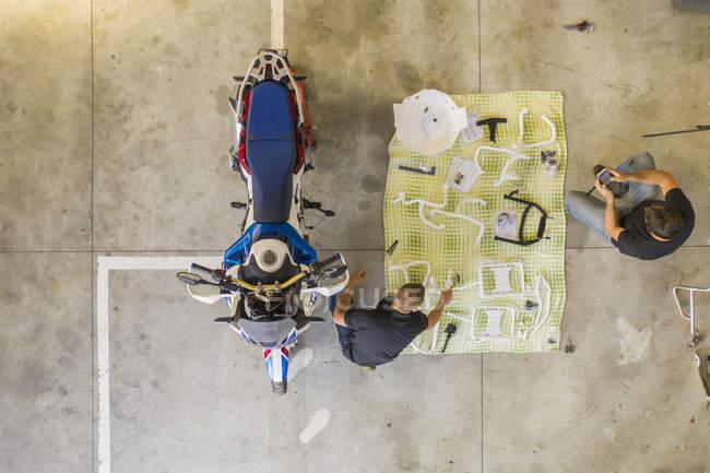 Deux hommes arrangeant des articles à côté d'une motocyclette en atelier — Photo de stock
