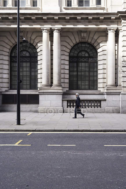 UK, London, senior businessman walking on pavement — Stock Photo