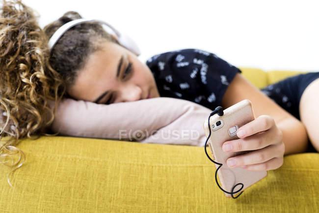 Chica acostada en el sofá de casa escuchando música con auriculares y teléfonos inteligentes. - foto de stock