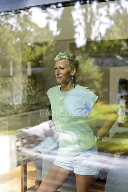 Porträt einer Frau mit kurzen Haaren, die aus dem Fenster schaut — Stockfoto