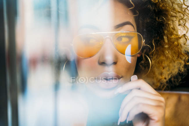 Portrait of fashionable young woman wearing yellow sunglasses — Stock Photo