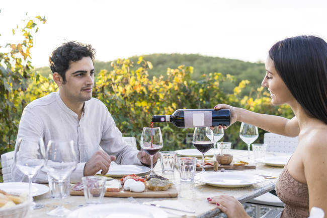 Italy, Tuscany, Siena, young couple having dinner in a vineyard with red wine — Foto stock