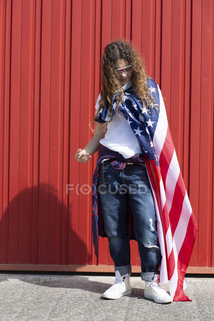 Girl standing at red wall with American flag — Stock Photo