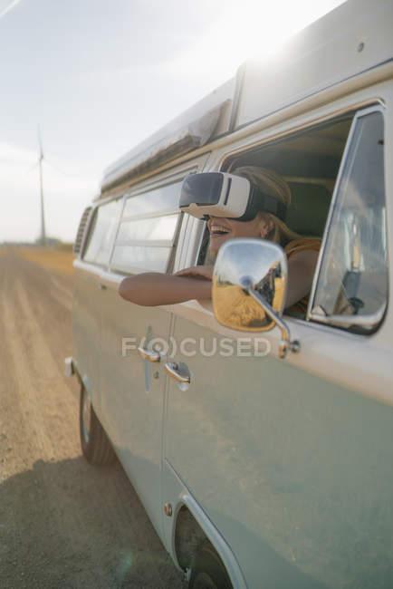 Счастливая женщина в очках VR, высунутая из окна фургона. — стоковое фото