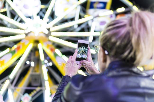 Visão traseira da mulher tirar foto da roda grande com smartphone na feira — Fotografia de Stock