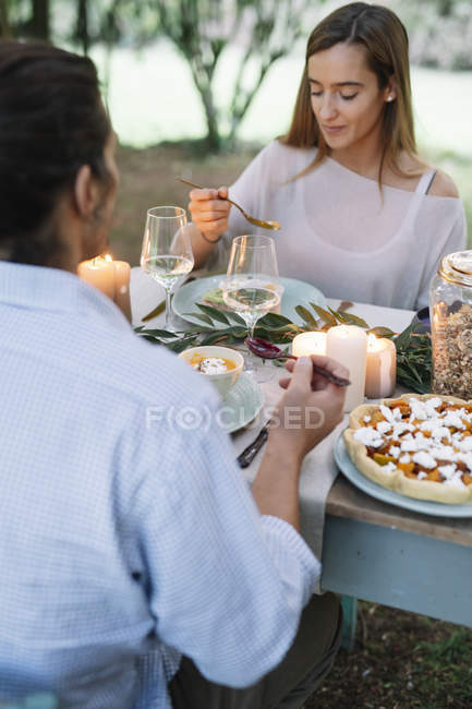 Couple having a romantic candlelight meal in garden — Stock Photo