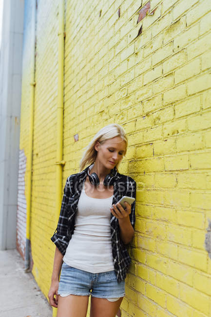 Young woman checking cell phone at yellow brick wall — Stock Photo