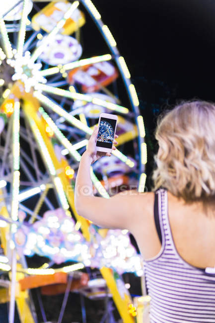 Back view of teenage girl taking photo of big wheel at fair — Stock Photo