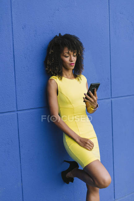 Portrait of fashionable businesswoman leaning against blue wall looking at cell phone — Stock Photo