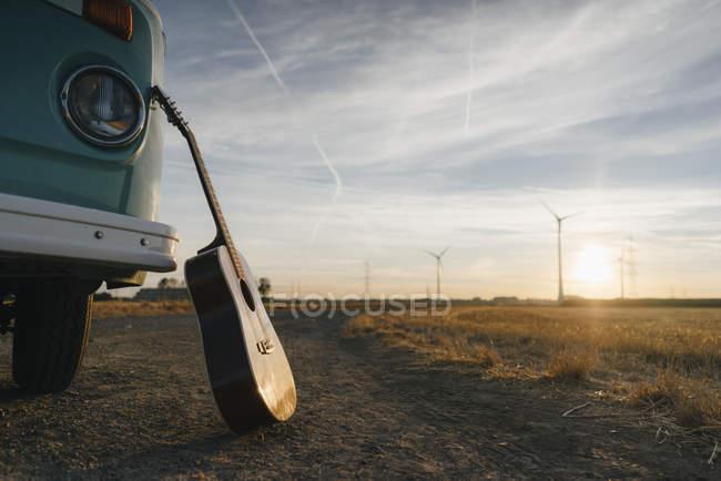 Гитара прислонившись к автофургоне ван в сельской местности с ветровыми турбинами на закате — стоковое фото