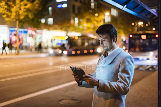 Businessman with digital tablet standing at a bus stop at night — Stock Photo