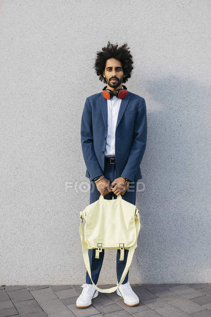 Portrait of stylish young businessman with bag and headphones at a wall — Stock Photo
