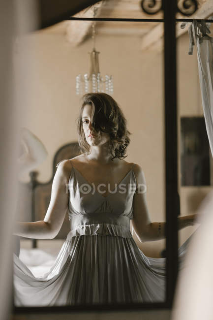 Young woman wearing grey dress and looking in mirror — Stock Photo
