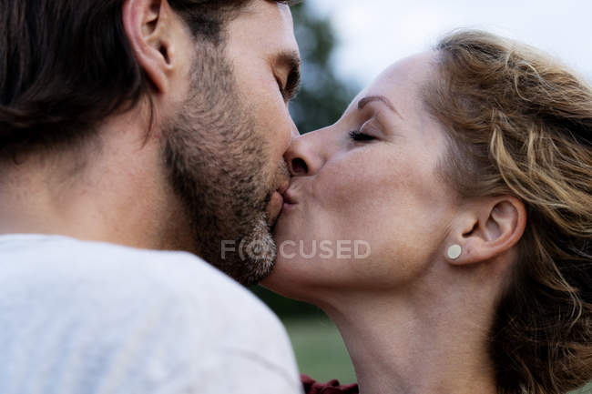 Affectionate couple kissing in nature — Stock Photo