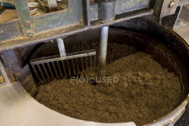 Graines de citrouille chauffées dans un récipient d'agitateur dans un moulin à huile — Photo de stock