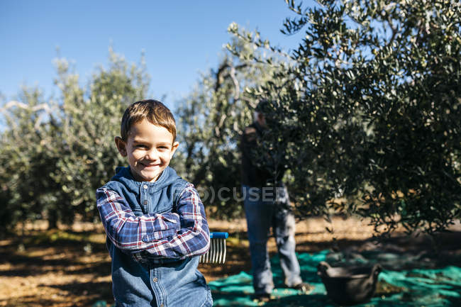 Portrait of smiling boy with his grandfather in olive orchard — Stock Photo