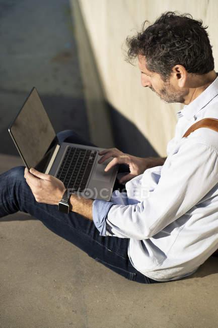 Älterer Mann sitzt auf Stufen und benutzt Laptop — Stockfoto