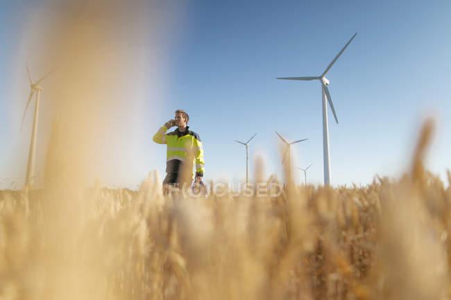Інженер стояв у полі на ВЕС і розмовляв по мобільному телефону — стокове фото