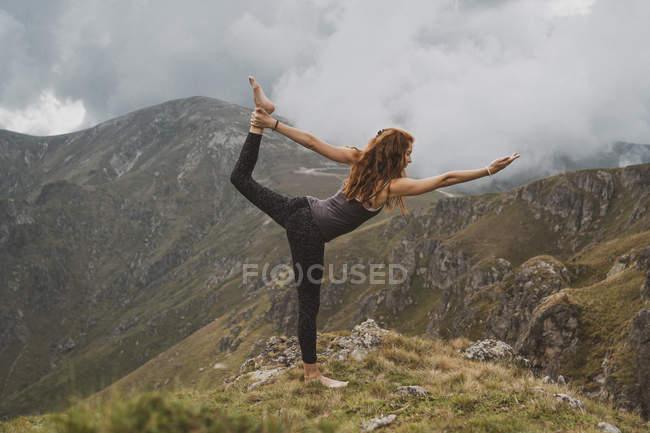 Рыжая женщина, занимающаяся йогой на вершине горы — стоковое фото