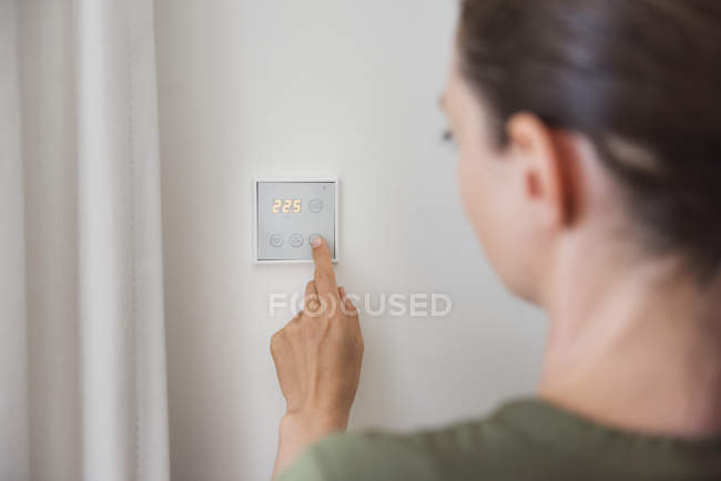 Femme utilisant un commutateur intelligent sur le mur — Photo de stock