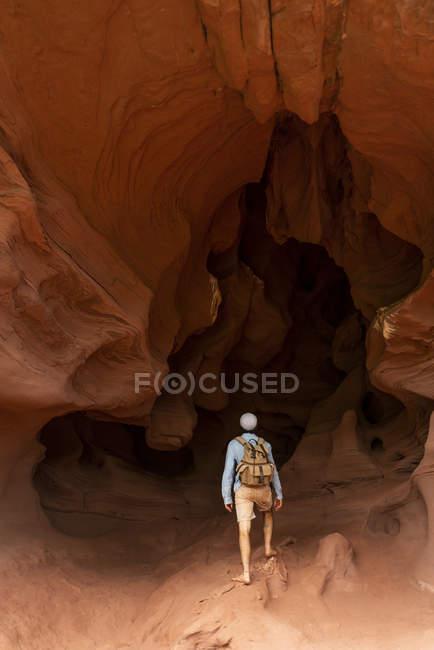 Jovem com mochila, olhando para a caverna, visão traseira — Fotografia de Stock