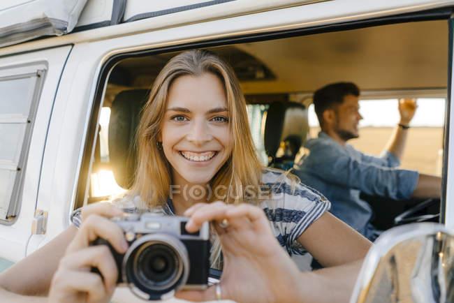 Ritratto di donna felice con macchina fotografica appoggiata al finestrino di un camper con uomo alla guida — Foto stock