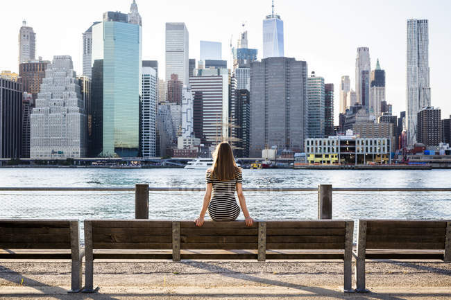 USA, New York, Brooklyn, back view of woman sitting on bench in front of East River and skyline of Manhattan — Stock Photo