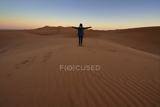 Morocco, back view of woman sitting on desert dune at twilight — Stock Photo