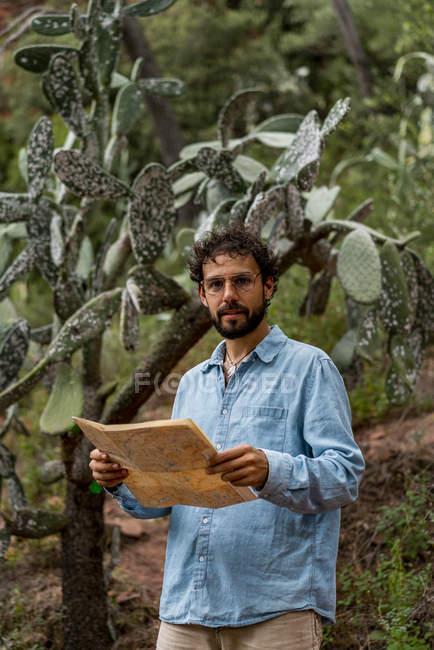 Молодий чоловік, що стоїть на природі, дивлячись на карту — стокове фото