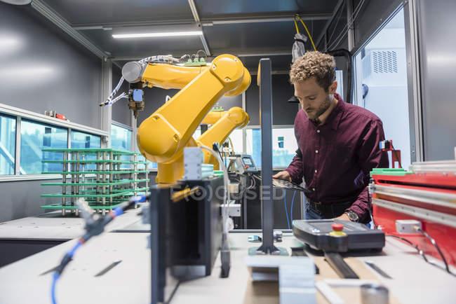 Empresario revisando robot industrial en empresa de alta tecnología - foto de stock