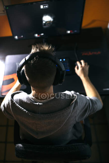 Young man sitting at his PC, playing computer games — Stock Photo