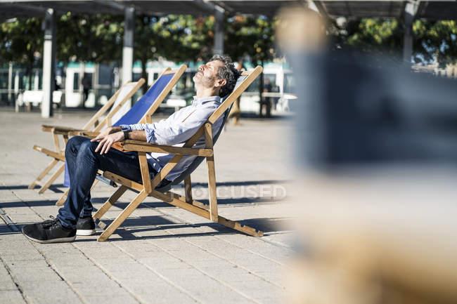 Reifer Mann entspannt sich im Liegestuhl auf einem Platz in der Stadt — Stockfoto