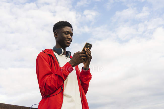 Young man with headphones, reding text messages on his smartphone — Stock Photo