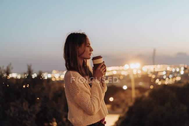 España, Barcelona, Montjuic, joven sosteniendo la bebida para llevar al atardecer con luces de la ciudad en el fondo - foto de stock